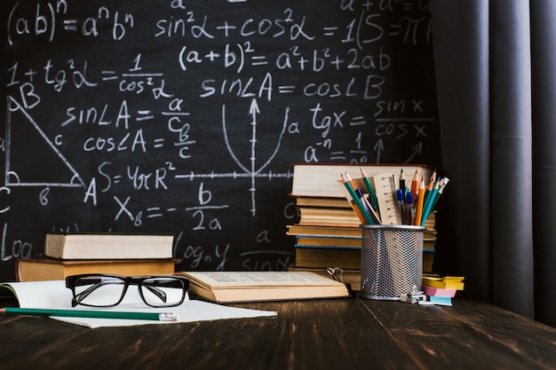 School desk in classroom, with books on background of chalk board with written formulas