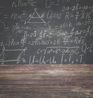 블랙 보드 배경에 흰색 분필로 작성된 수학 공식이있는 학교 책상