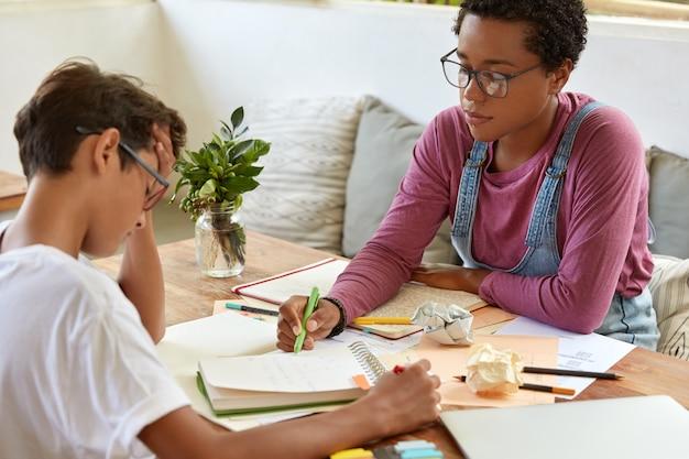 学校教育と家庭教師の概念。黒人の賢いアフリカ系アメリカ人女性の横向きのショットは、頭痛があり、フリップチャートや図を理解できない男子生徒のいくつかの質問に答えます