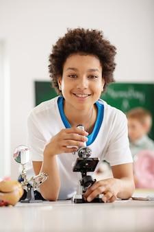 학교 교육. 학교에서 공부하는 동안 생물학 수업을받는 기쁘게 좋은 소년