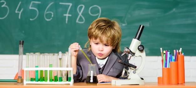 학교 교육. 생물학적 분자를 탐색합니다. 천재 유아. 기술 및 과학 개념입니다. 학교 교실에서 현미경과 시험관 근처에 있는 소년. 아이는 학교에서 생물학과 화학을 공부합니다.