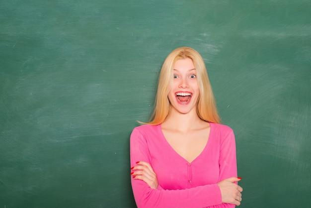 学校教育。正式な教育。創造性と新鮮なアイデア。大学教育。教育の概念。応募する大学を選択してください。女の子の愛らしい学生スタンド教室黒板背景コピースペース。