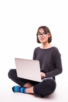 学校、教育、インターネット、技術コンセプト-ラップトップコンピューターで床に座っている若い十代の少女