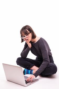Концепция школы, образования, интернета и технологий - молодая девушка-подросток сидит на полу с портативным компьютером