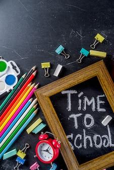 School education supplies on chalkboard backdrop