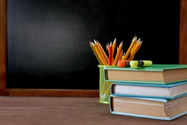 Школьное оборудование на столе на фоне доски