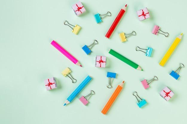 Школьное оборудование. разнообразие школьных принадлежностей. цветной карандаш и скрепка. концепция подготовки к школе. шаблон.