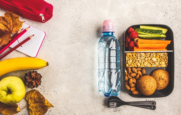 School flat lay. healthy meal prep containers with fruits, berries, snacks and vegetables.