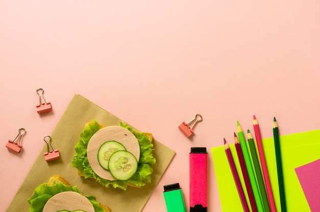 School flat lay with stationery and sausage sandwiches on a pink background