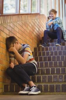 School friend bullying a sad boy in school corridor