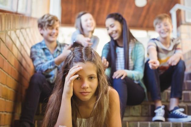 Школьные друзья издеваются над грустной девушкой в школьном коридоре
