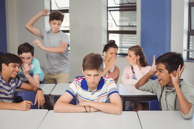 School friends bullying a sad boy in classroom