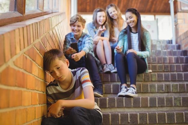 School friends bullying a sad boy in school corridor