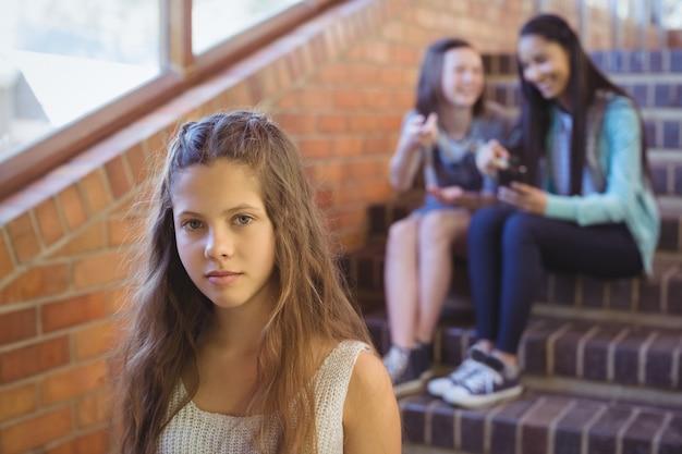 School friends bullying a sad girl in school corridor
