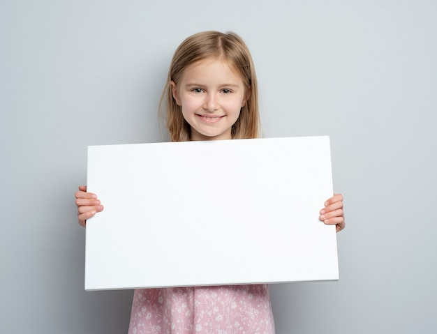 空白の白いポスターを保持している学校の女の子