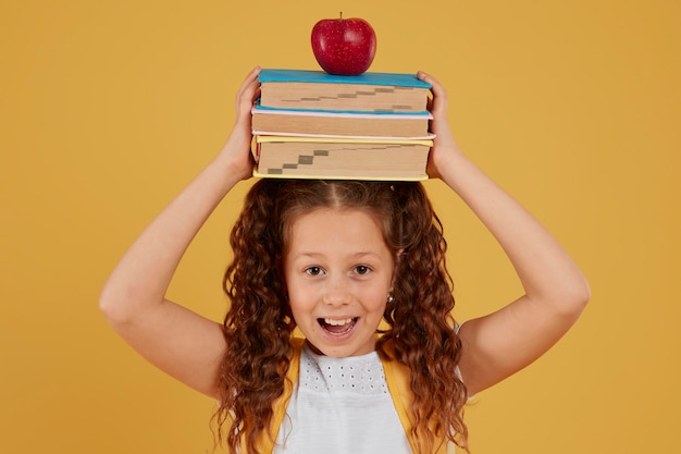 Школьница держит книги и яблоко на голове