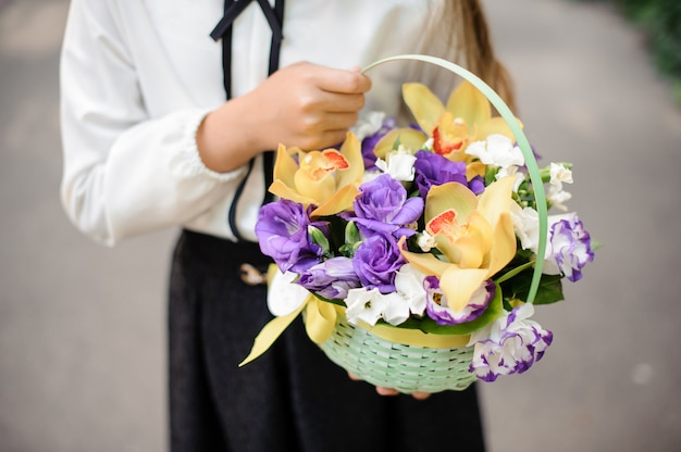 School girl holding a cute wicker basket full of bright colorful flowers