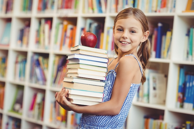 School girl holding stack of books in library
