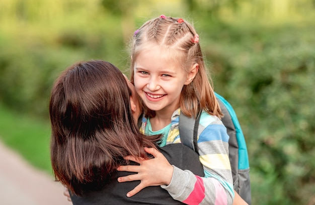School girl hugging mother after classes in sunny park