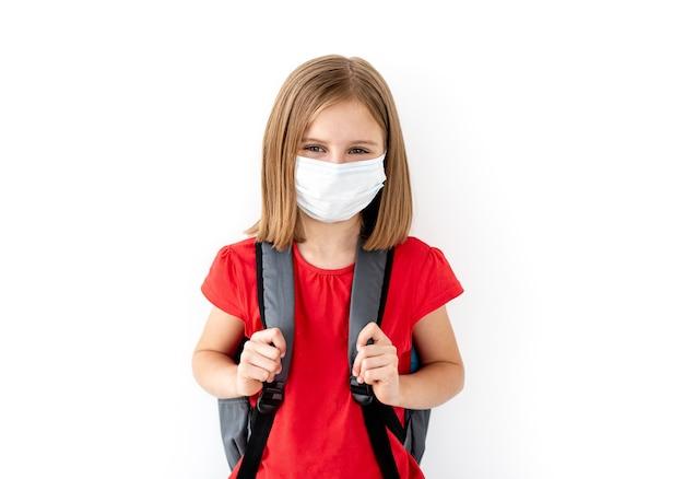 白の医療フェイスマスクの学校の女の子