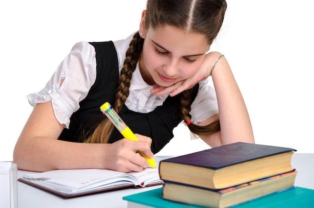 제복을 입은 여고생이 그녀의 노트북에 쓰고 흰색 배경에 고립 된보고