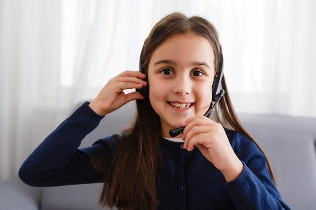 女子高生はオンラインで勉強しています。ホームスクーリング。遠隔教育。少女は手を挙げて先生の質問に答えます。