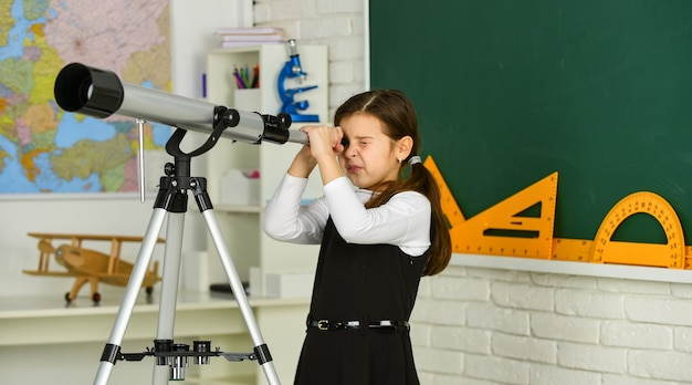 Школьница, глядя в телескоп. маленькая девочка с помощью телескопа. телескоп на штативе. набор школьных предметов. школьный урок астрономии. изучение космоса и планет новых галактик.