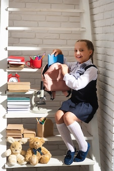 学校に戻る子供のための学校教育のためのバックパックを準備している女子高生小さな女子高生コレクション...