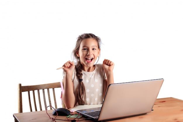 表情豊かな感情的な顔を持つラップトップでテーブルに座っている学校の女の子