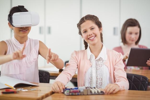 Школьница сидит в классе с помощью гарнитуры виртуальной реальности