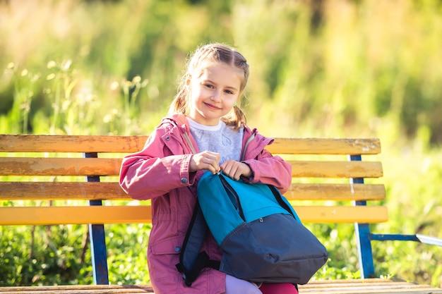 Школьница сидит на скамейке в солнечном парке с рюкзаком после уроков