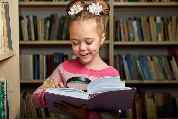 図書館で百科事典を持って立っている女子高生、本を読んで、脳のための新しい情報を取得します