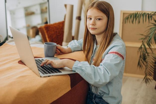 Школьница учится дома, дистанционное обучение