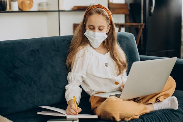 マスクを身に着けて自宅で勉強している女子高生、遠隔教育