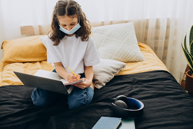 School girl studying at home wearing mask, distant learning
