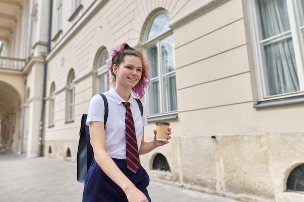 Школьница гуляет с рюкзаком и чашкой кофе