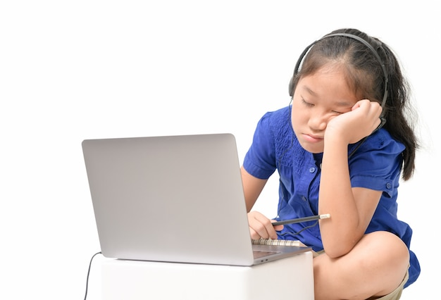 School girl watching online education classes feeling bored and depressed at home.