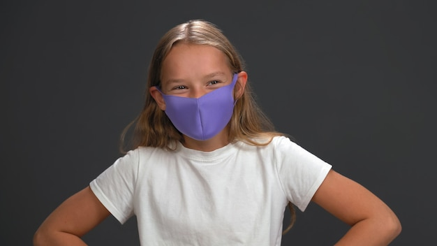 Школьница в синей многоразовой маске для лица в белой футболке улыбается глазами