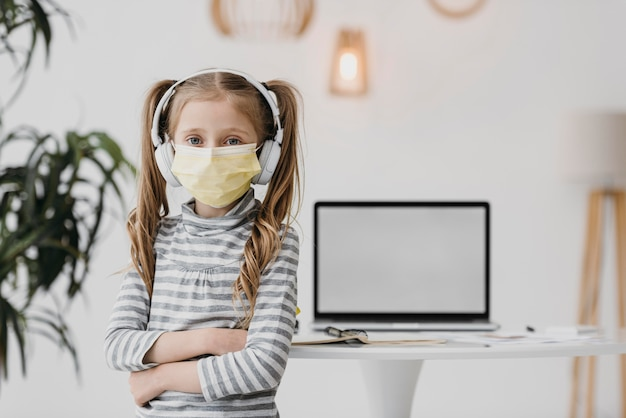 School girl wearing medical mask indoors