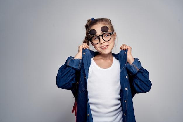 ピンクのバックパックと灰色のサングラスを持つ学校の女の子