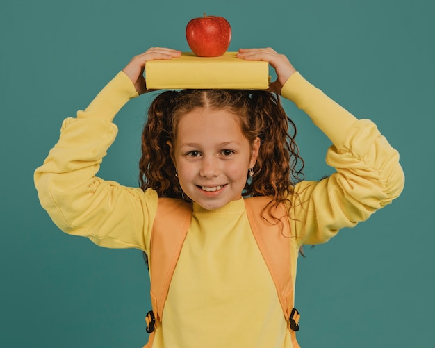 School girl with yellow shirt holding a book and an apple