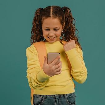 Школьница в желтой рубашке смотрит на свой телефон