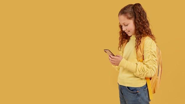 Школьница в желтой рубашке смотрит в копировальное пространство телефона