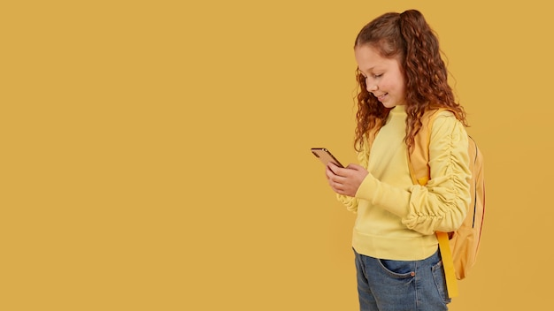 School girl with yellow shirt looking at the phone copy space