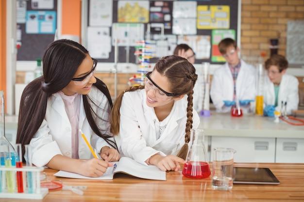 학교에서 실험실에서 실험하는 동안 저널 책에 쓰는 여고생