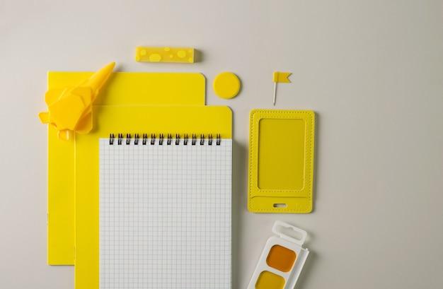 黄色の学用品は灰色の背景にあります。ノートブック、檻の中のノートブック、バッジ、消しゴム、鉛筆削り-フラットなレイアウトで学校に戻るコンセプト、テキストのコピー Premium写真