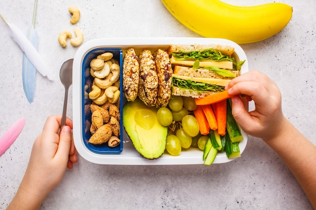 School healthy lunch box with sandwich, cookies, fruits and avocado on white background.