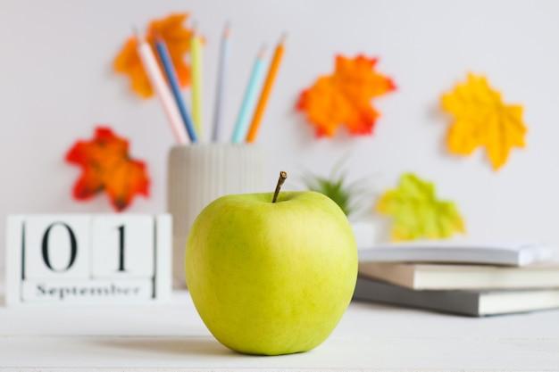 학교 건강 간식 녹색 사과는 다양한 학용품이 있는 탁자 위에 서 있습니다.