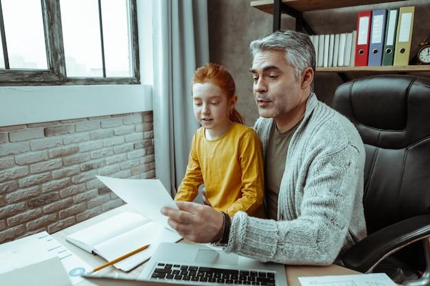 Школьное домашнее задание. приятный приятный мужчина держит лист бумаги, помогая дочери с уроками