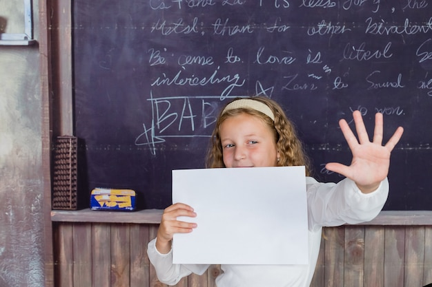 School is a happy place happy small child holding blank paper on blackboard background little girl h...